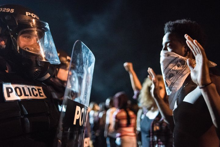 Police officers face off with protestors on the I-85 (Interstate 85) during protests following the death of a man shot by a p