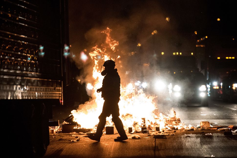A police officer in riot gear walks past a fire on the I-85 during protests.