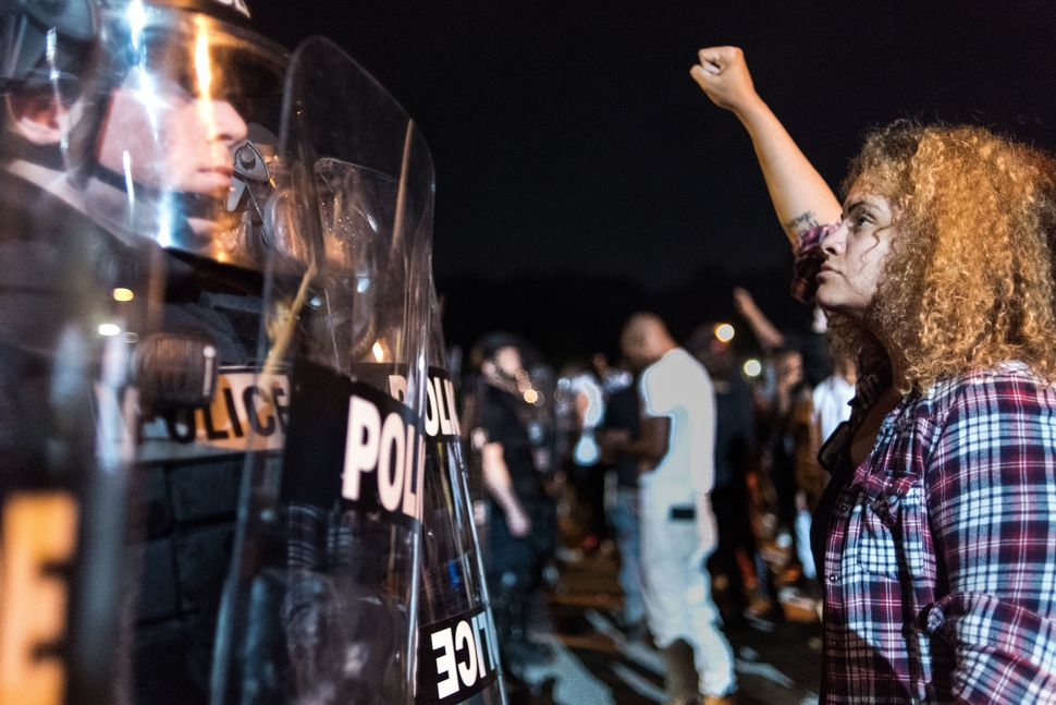 Police officers face off with protesters on the I-85 during protests.