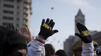 Lesley McSpadden (C), mother of Ferguson shooting victim Michael Brown, holds up her hands with gloves that say 'Don't Shoot' during the 'Justice For All' march in Washington, DC, December 13, 2014.  Thousands of people descended on Washington to demand justice Saturday for black men who have died at the hands of white police, the latest in weeks of demonstrations across the United States.       AFP PHOTO/JIM WATSON        (Photo credit should read JIM WATSON/AFP/Getty Images)