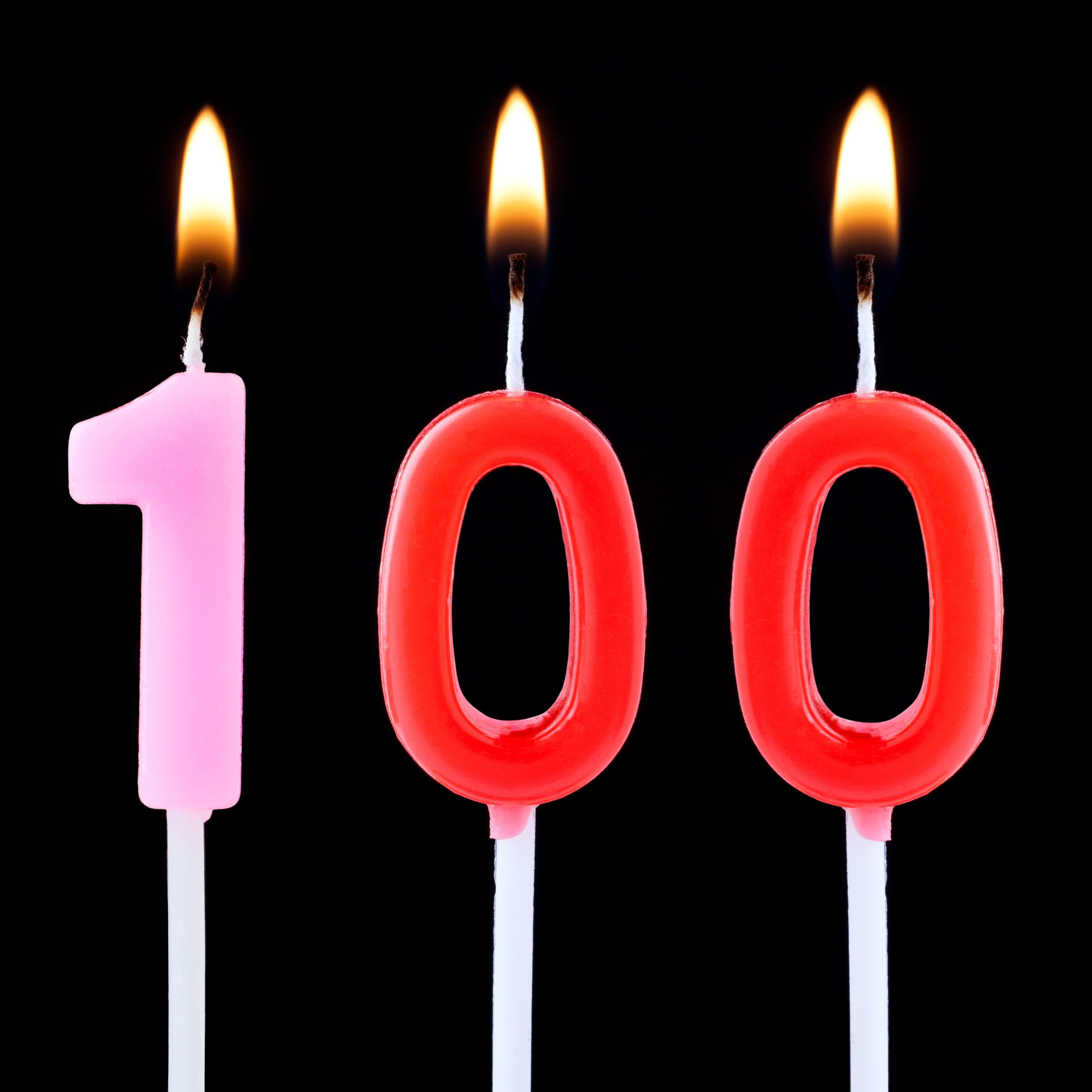 Number one hundred birthday candle isolated on a black background.