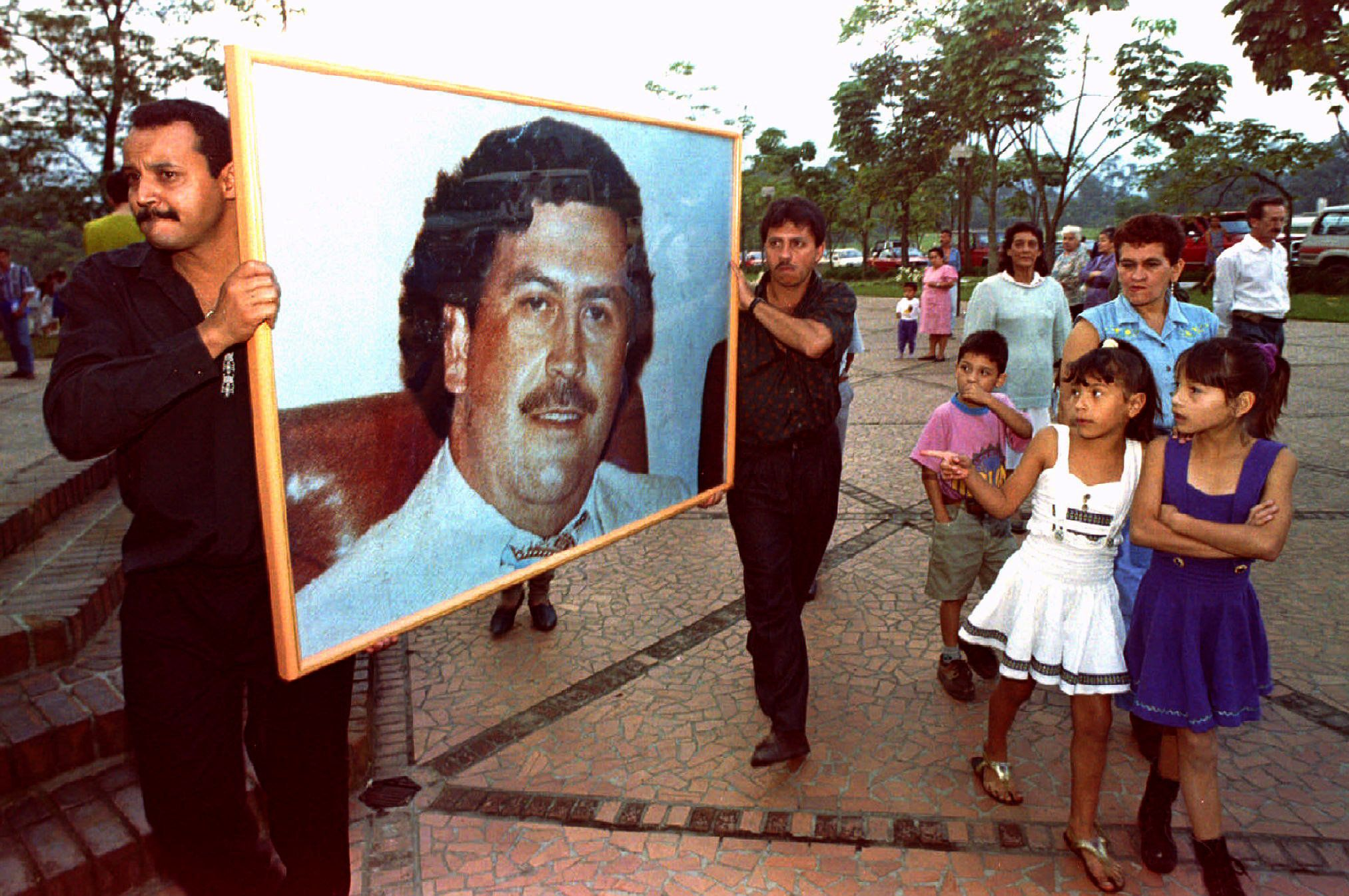 Two men carry a picture of Pablo Escobar through the streets of Medellin December 2, on the first anniversary of his death. Hundreds of admirers packed a memorial service for the slain cocaine king, proclaiming undying loyalty to the dead drug lord