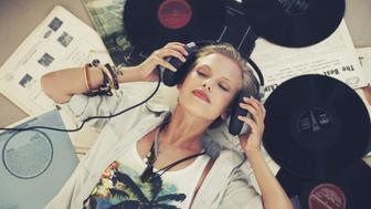 A young woman listening to music while lying on her back and surrounded by records