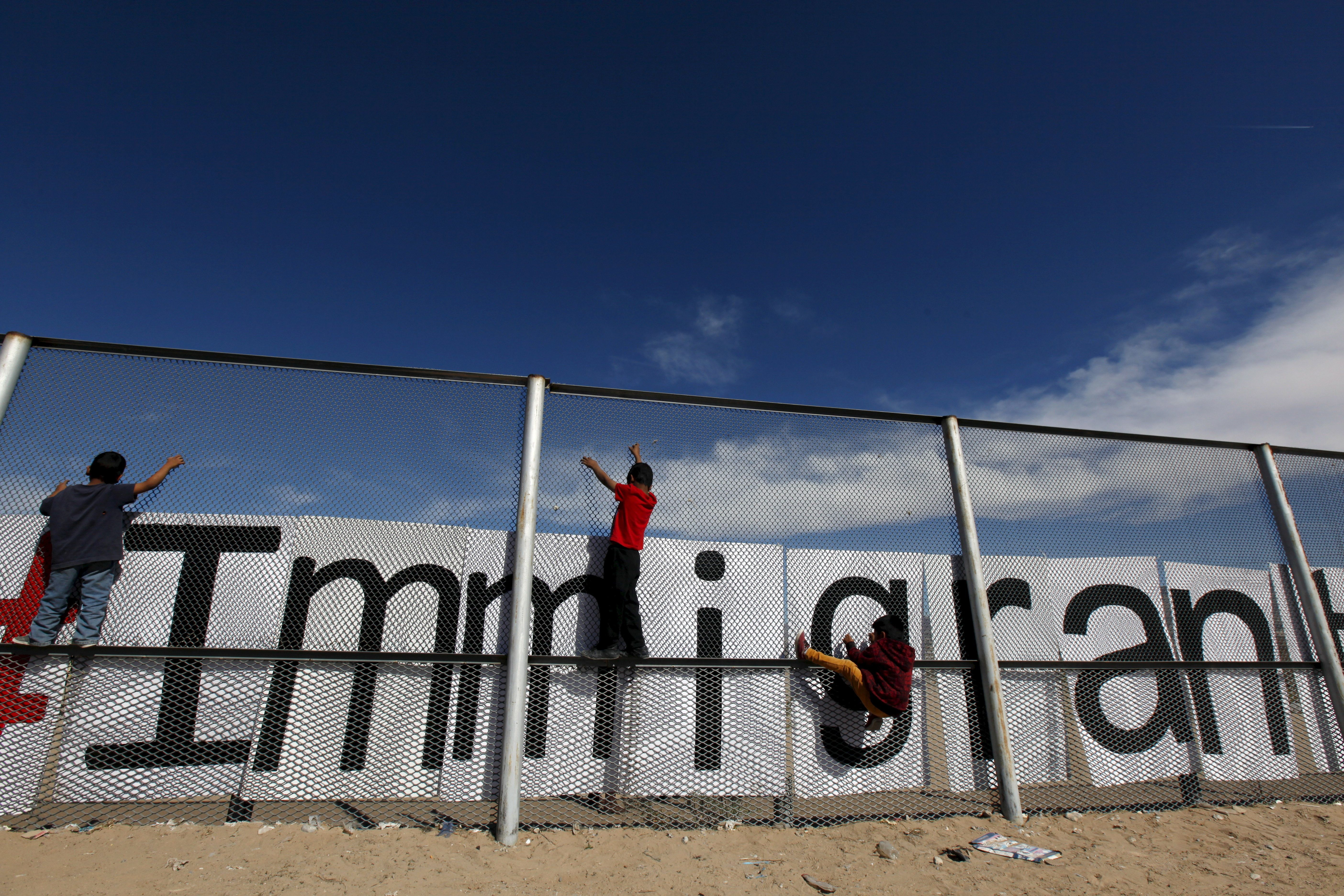 Children climb onthe border fence between Ciudad Juarez, Mexico, and El Paso, Texas, during a bi-national Mass in suppo