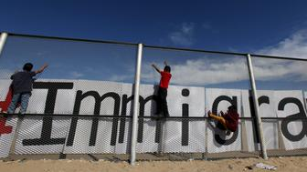 Children climb up the border fence between Ciudad Juarez and El Paso, United States, during a bi-national Mass in support of migrants in Ciudad Juarez, Mexico, February 15, 2016. According to the organizers of the event, the Mass was organized to bring together dozens of families of Mexican migrants living in the U.S. and who, based on their immigration status, will not be able to join their families in Mexico when Pope Francis celebrates Mass in Ciudad Juarez on February 17.  REUTERS/Jose Luis Gonzalez