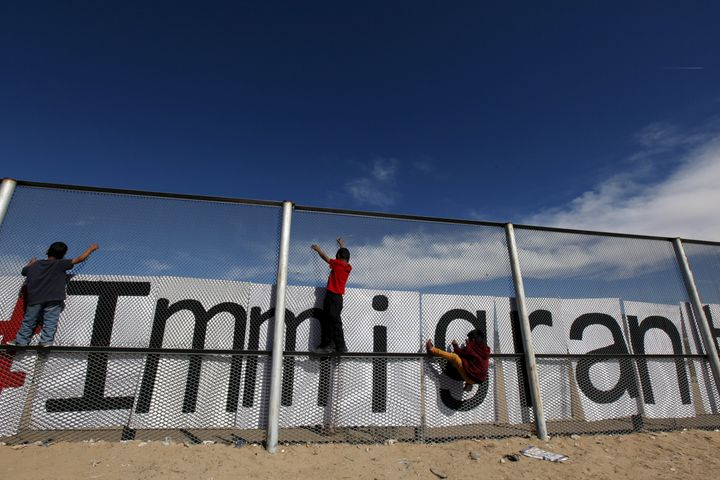 Children climb on the border fence between Ciudad Juarez, Mexico, and El Paso, Texas, during a bi-national Mass in suppo