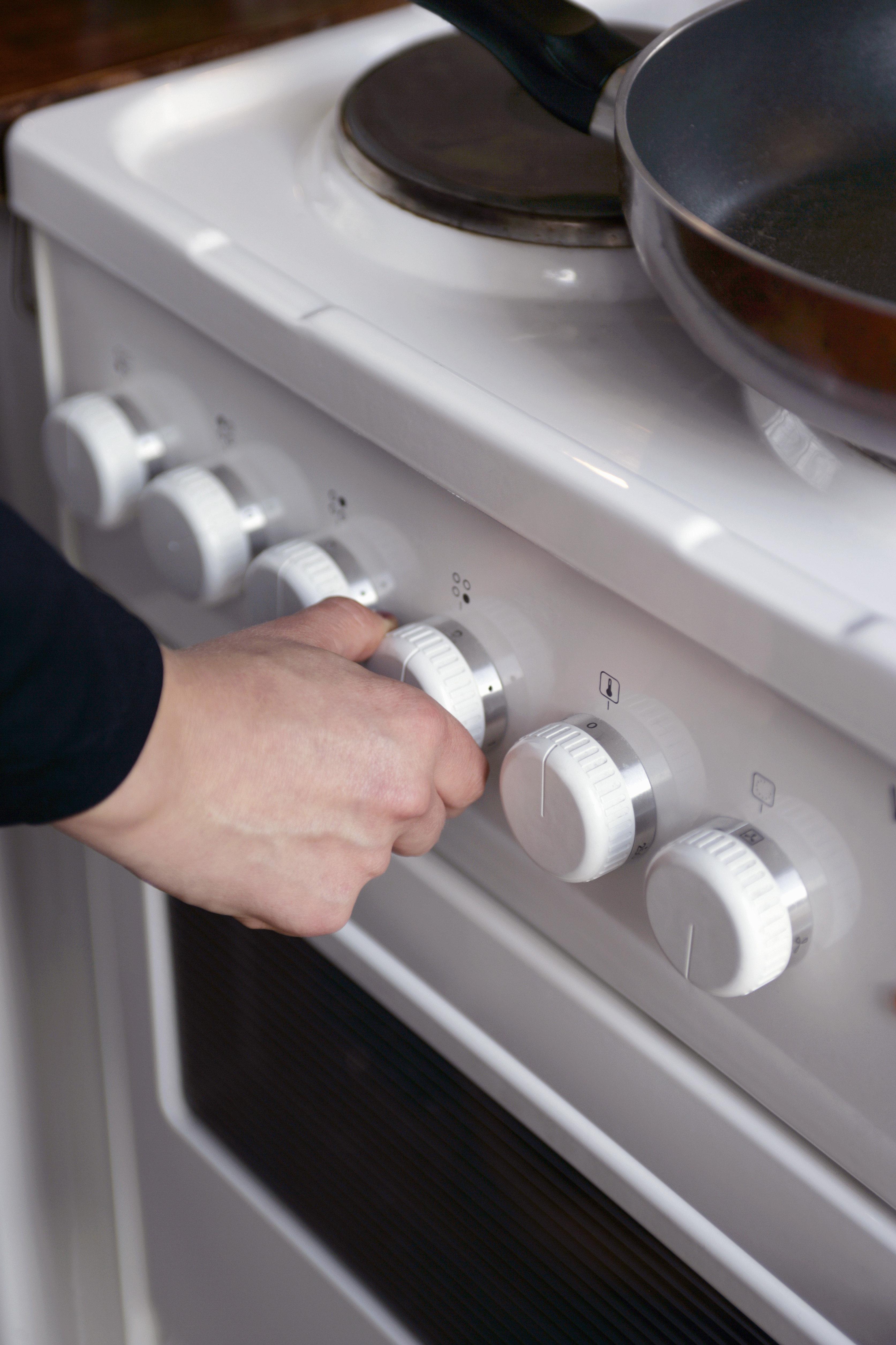 A woman adjusting an stove