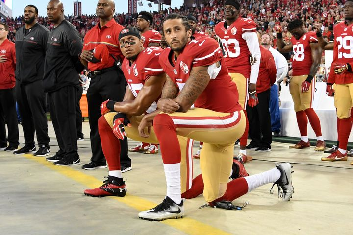 Colin Kaepernick #7 and Eric Reid #35 of the San Francisco 49ers kneel in protest during the national anthem prior to playing