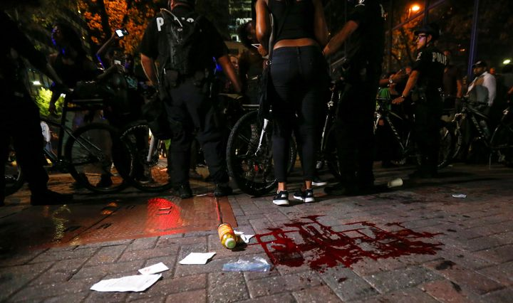 Blood covers the pavement where a person was shot in uptown Charlotte, NC during a protest of the police shooting of Keith Sc