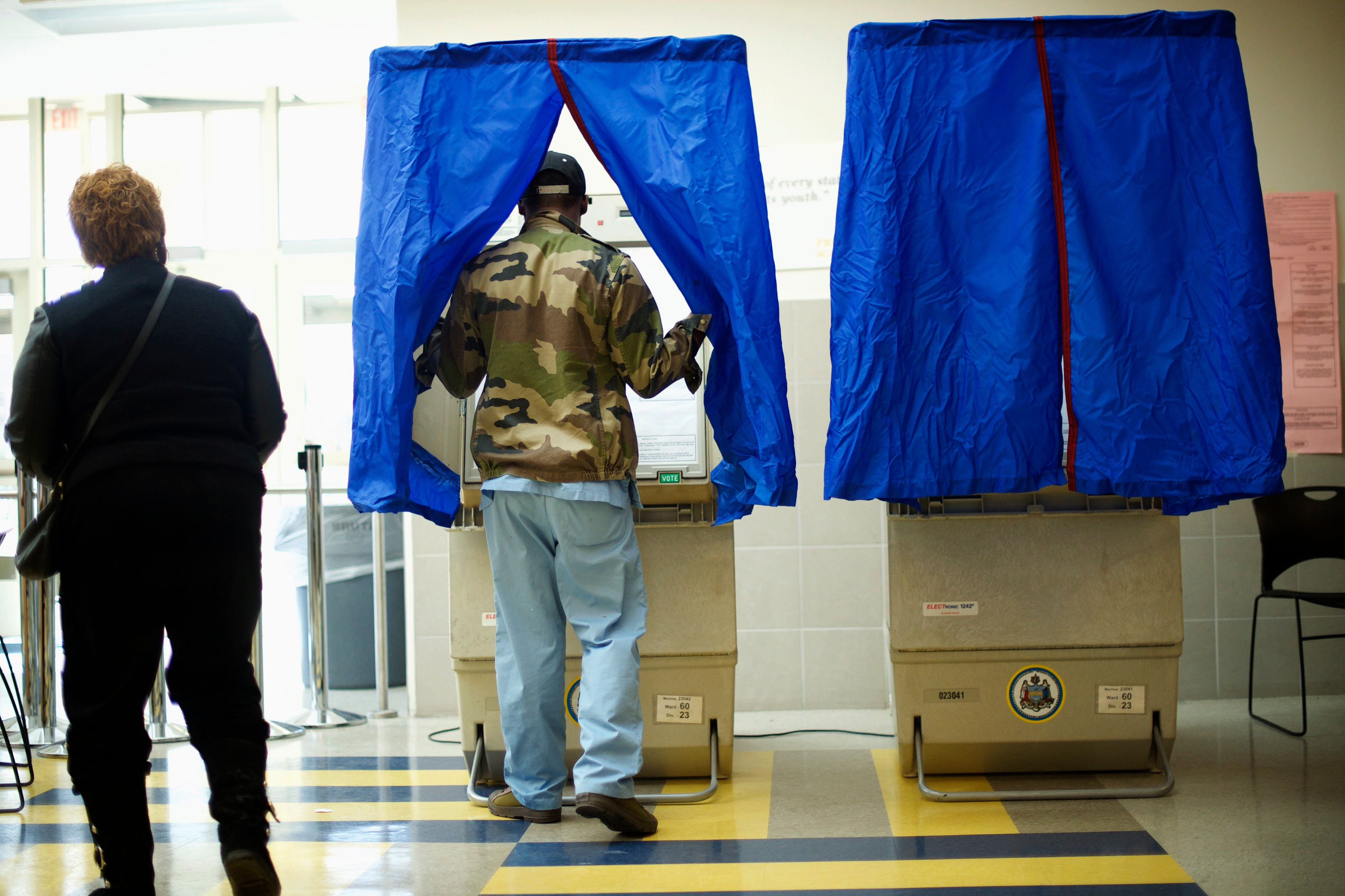 A man enters a voting booth at West Philadelphia High School on U.S. midterm election day morning in Philadelphia, Pennsylvania, November 4, 2014.  REUTERS/Mark Makela (UNITED STATES - Tags: POLITICS ELECTIONS)