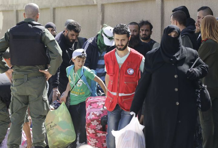 Syrian army and police forces stand guard as members of the Red Crescent help the families of opposition fighters evacuate at