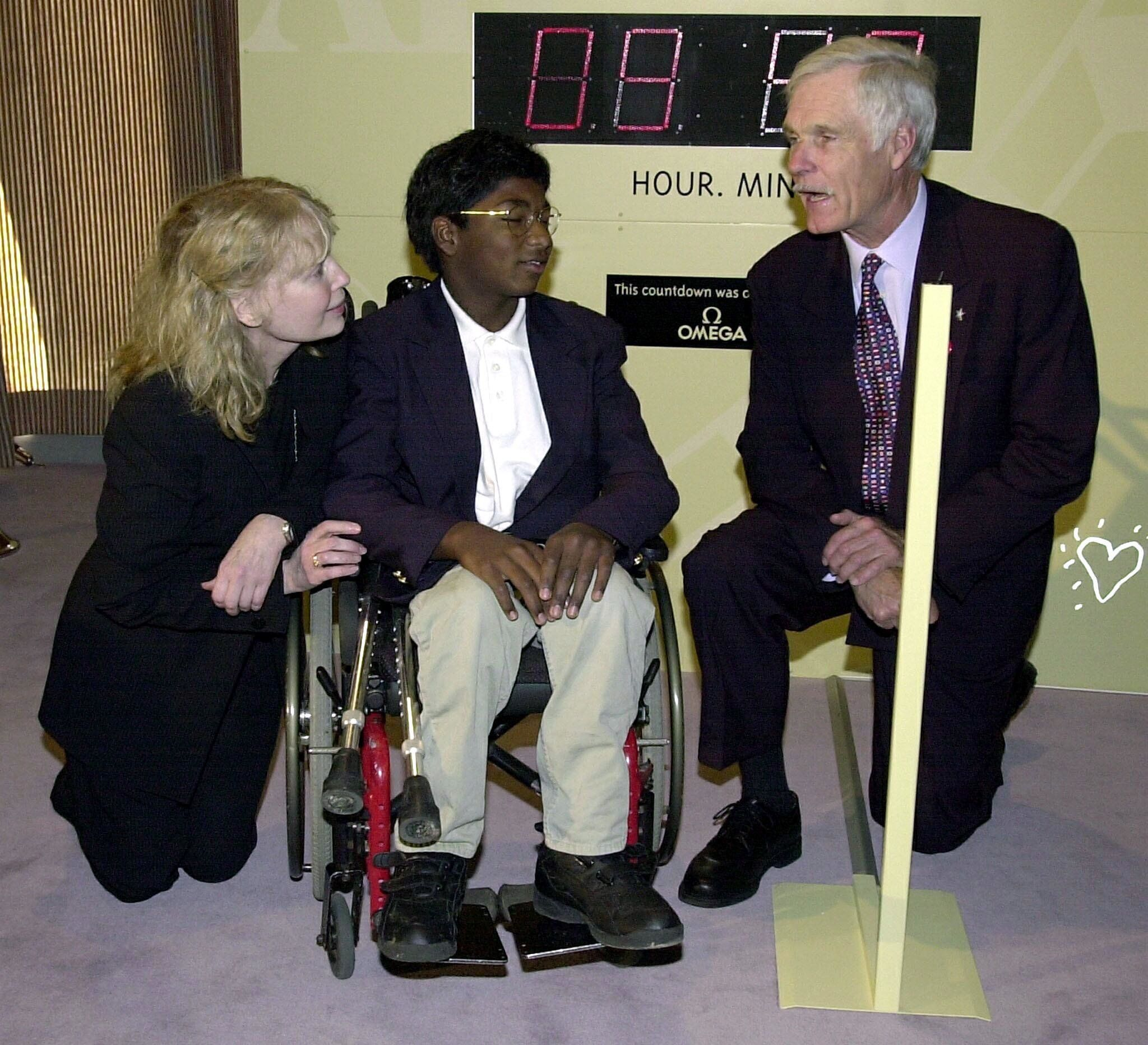 Mia Farrow and her adopted son Thaddeus, who suffers from polio, talk with media mogul Ted Turner before a United Nations con