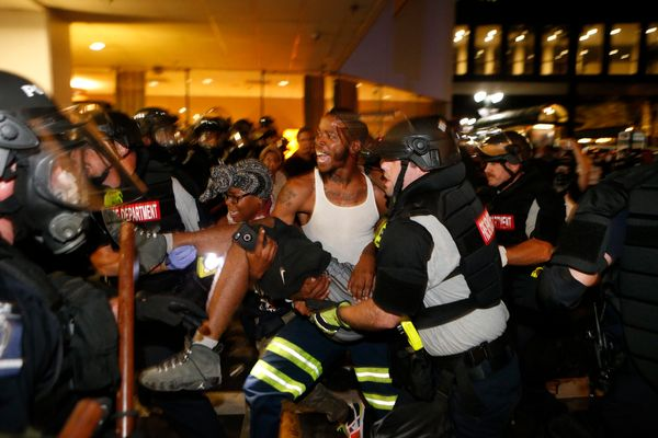 Police and demonstratorscarry a seriously wounded individualinto the parking area of the the Omni Hotel during a