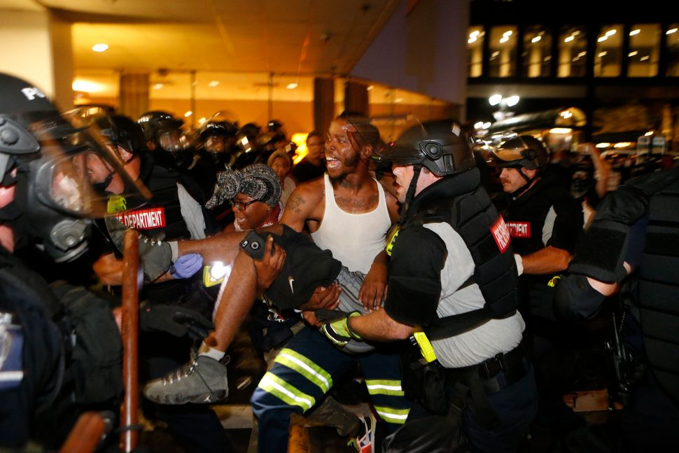 Police and demonstrators carry a seriously wounded individual into the parking area of the the Omni Hotel during a