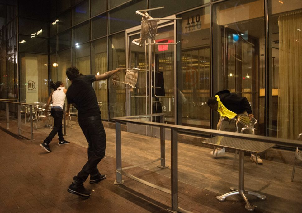 Protesters throw chairs at a restaurant during a demonstration against police brutality.
