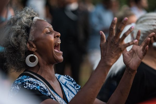 A woman gestures as she participates in a protest at Marshall Park.