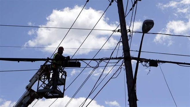 Many cities and states are pushing to expand broadband access to underserved areas. Above, a cable employee works on a fiber optic line in New York.