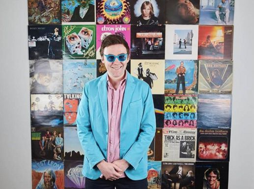 Tom Cridland, a music enthusiast, in front of a wall of vinyl records.