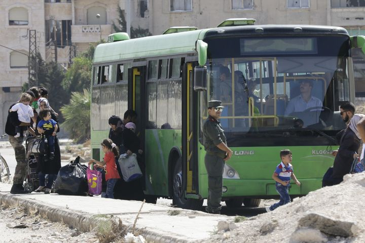 Families of opposition fighters board a bus at a Syrian army checkpoint on the edge of the rebel-held Waer neighbourhood in t