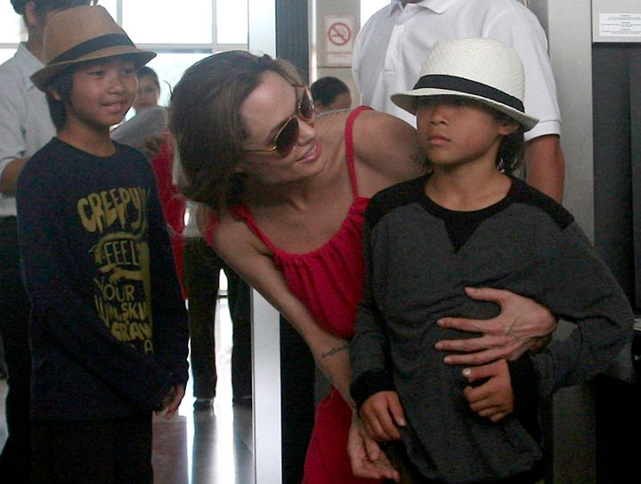 Hollywood actress Angelina Jolie (C) chats with her adopted son Pax Thien, from Vietnam, next to Maddox (L), from Cambodia, a