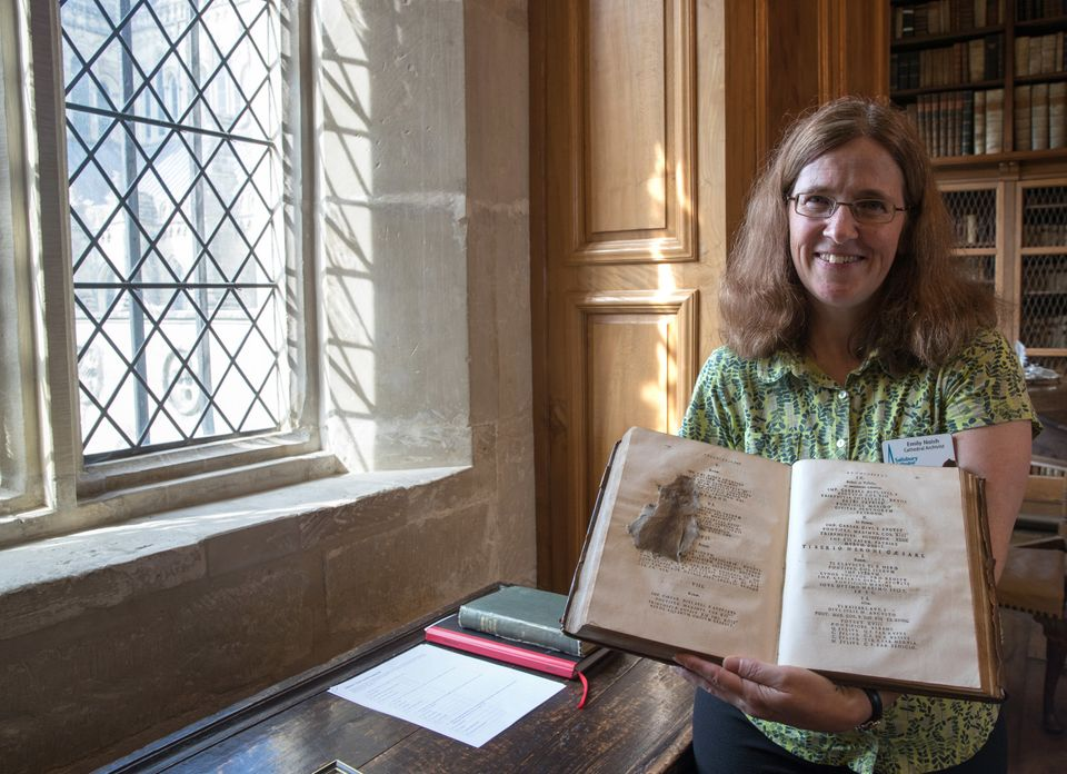 Cathedral Archivist Emily Naish holds up a book that contains a mouse that was squashed by 19th-century pupil at the Cathedra