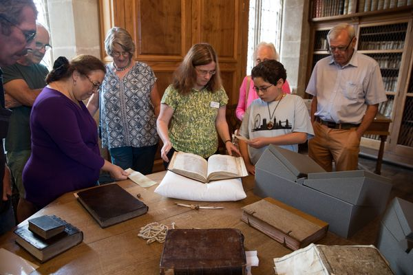 Cathedral Archivist Emily Naish (C) displays a book, one of a collection of 12th-century manuscript books originally forming