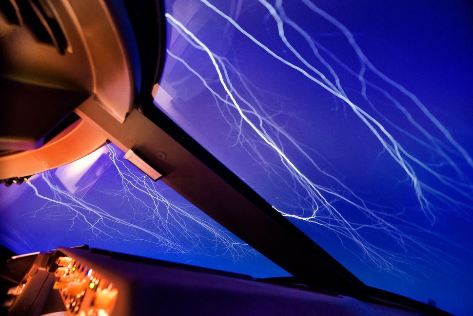 Lightning streaks across the sky like cracks in a windscreen.