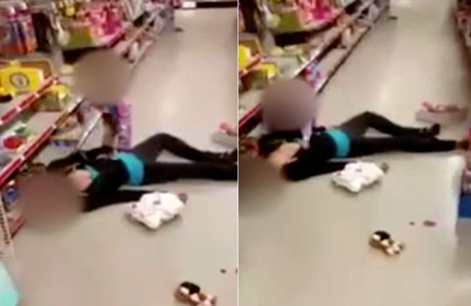 A little girl tries to wake her mother, whopassed out in a Massachusetts store on Sunday.