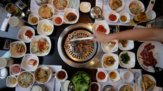 'aerial' shot of dining table at a Korean restaurant, with lots of bowls of panchan and other condiments.