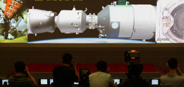 Scientists look at the screen showing the Shenzhou X manned spacecraft conducting docking with the orbiting...