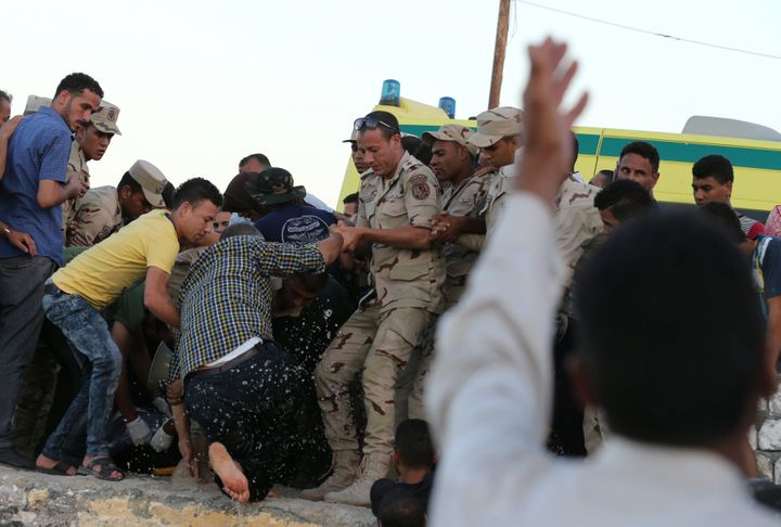 Egyptian army officers help a man up as they check the body of one of his relatives who arrived in a boat carrying migrants w