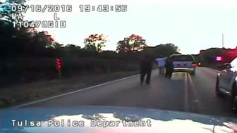 A still image captured from a dashcam video from Tulsa Police Department shows Terence Crutcher seen with his hands in the air followed by police officers during a police shooting incident in Tulsa, Oklahoma, U.S. on September 16, 2016. Video taken September 16, 2016.  Courtesy Tulsa Police Department/Handout via REUTERS    ATTENTION EDITORS - THIS IMAGE WAS PROVIDED BY A THIRD PARTY. EDITORIAL USE ONLY