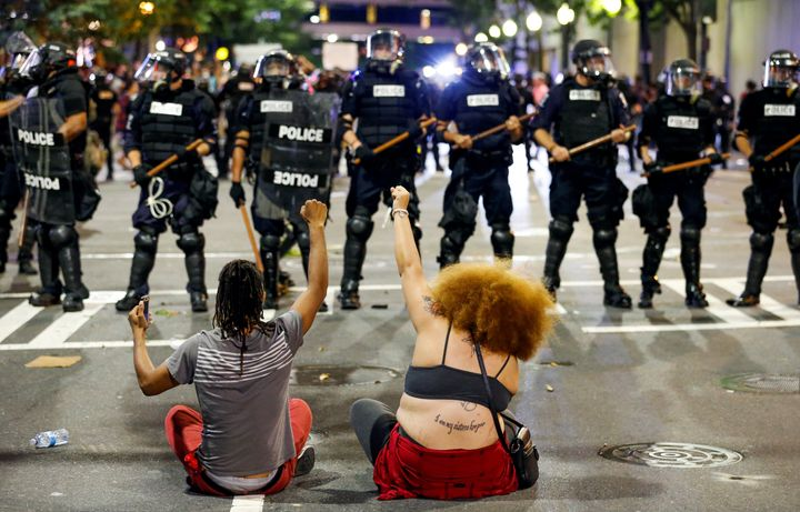 Protesters sit in front of police in riot gear during the Charlotte uprising.