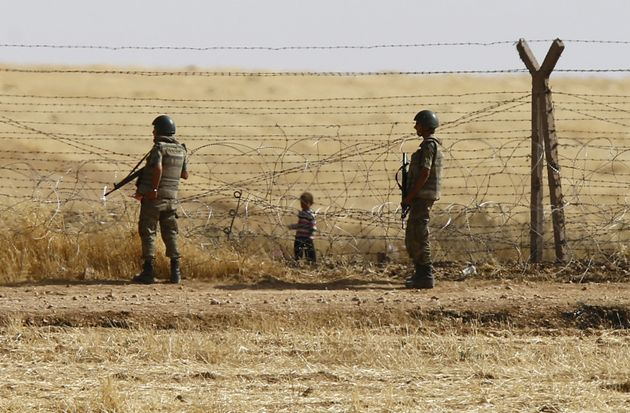 Turkish soldiers stand guard as a Syrian refugee boy waits behind the border fences to cross into Turkey,...