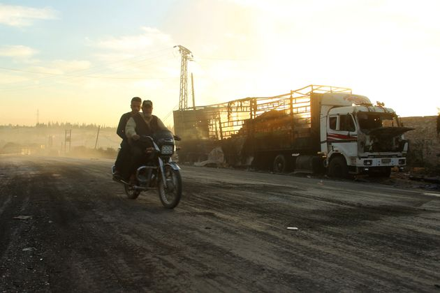 Men drive a motorcycle near a damaged aid truck after an airstrike on the rebel-held Urm al-Kubra town,...