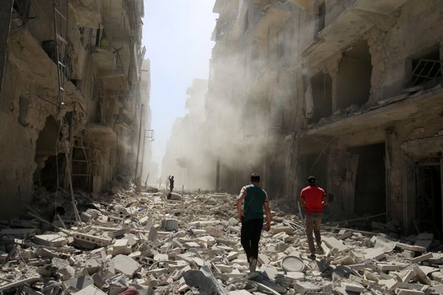Men inspect the damage after an airstrike on the rebel held al-Qaterji neighbourhood of Aleppo, Syria...