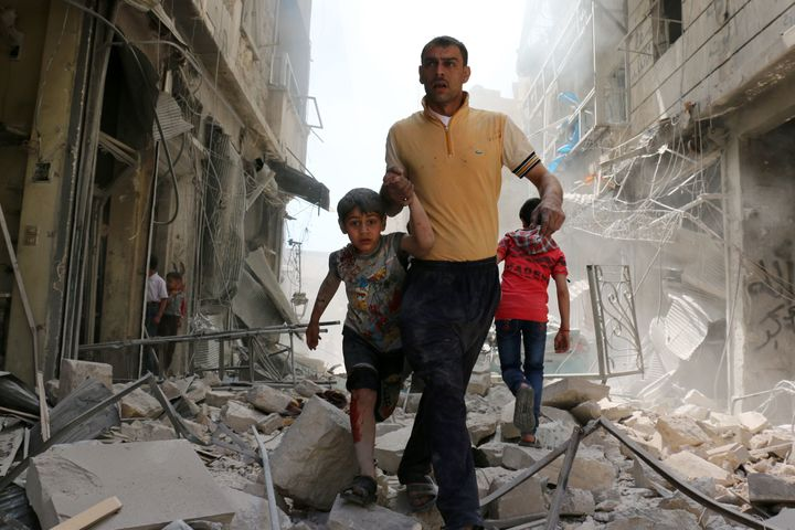 A Syrian man evacuates an area following a reported airstrike on April 22, 2016 in the rebel-held neighborhood of Hayy Aqyul