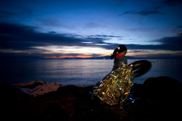 A Syrian girl holds on to a rubber float during sunrise after arriving on an inflatable boat with other refugees, crossing th