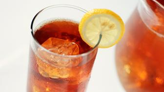 A Glass of Iced Tea with a Lemon Slice and Pitcher
