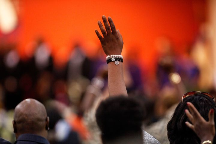 An attendee holds up their hand during the funeral.