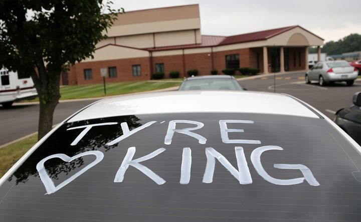 A car with its rear window painted is parked outside the First Church of God during the funeral of Tyre King.
