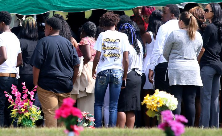 Mourners stand at the cemetery during the funeral of Tyre King.