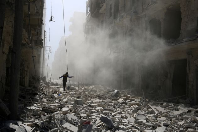 A man walks on the rubble of damaged buildings after an airstrike on the rebel held al-Qaterji neighbourhood...