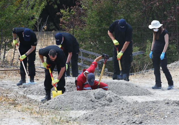 South Yorkshire Police search officers sift through piles of earth taken from an olive grove near the...