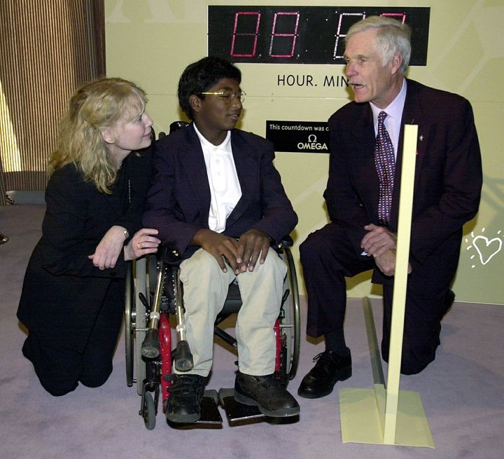 Mia Farrow and her adopted son Thaddeus speak with media mogul Ted Turner before a United Nations conference on the erad