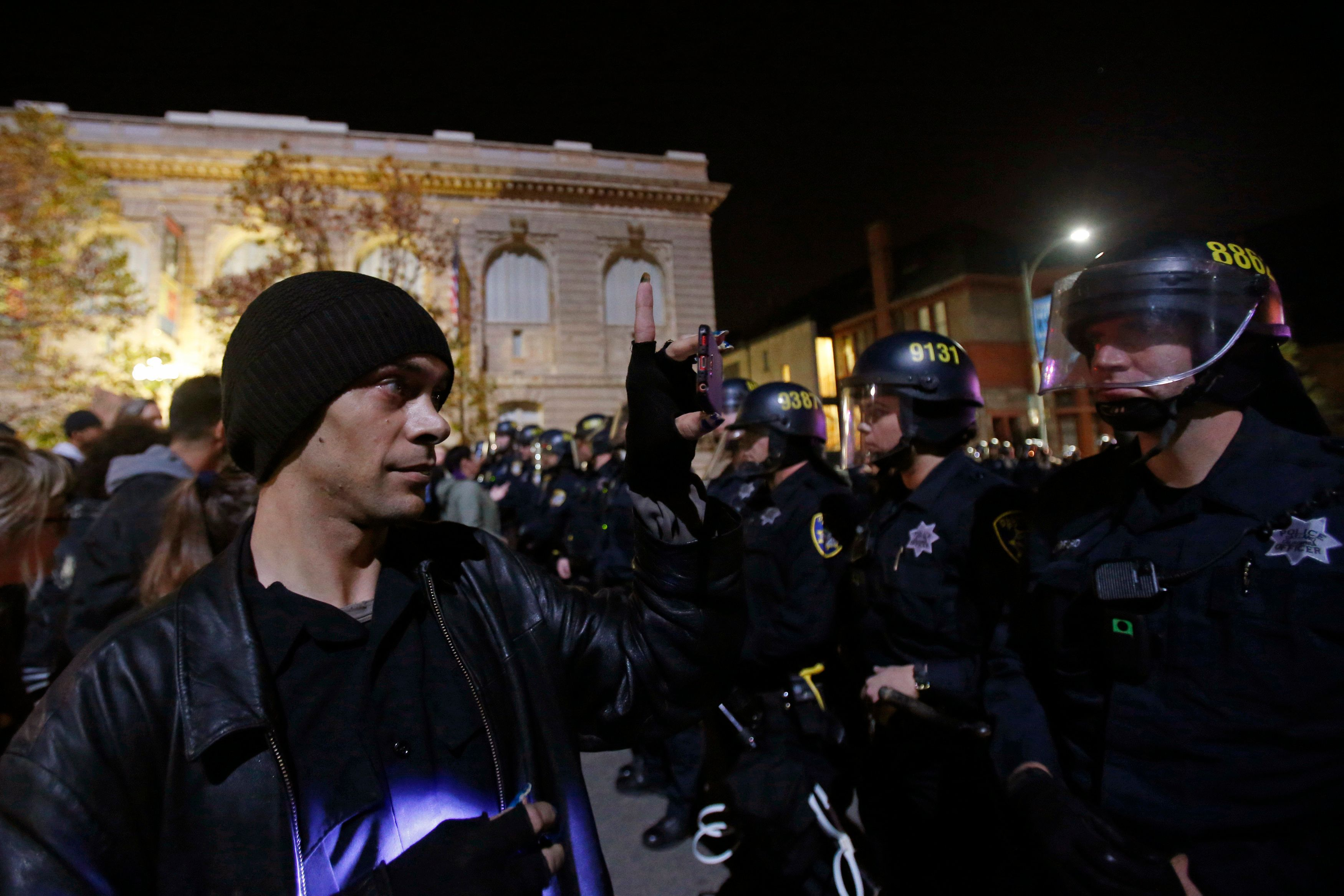 A protester records a video of police officers during a demonstration following the grand jury decision on Monday in the Ferguson, Missouri shooting of Michael Brown, in Oakland, California November 25, 2014. REUTERS/Stephen Lam  (UNITED STATES - Tags: CIVIL UNREST)