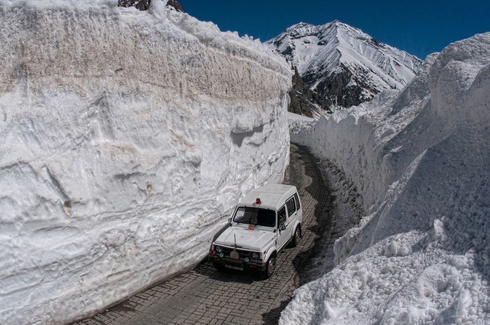 "A vehicle passes through the snow-cleared Srinagar-Leh highway. This mountain road is only open for about <a href=""http:"