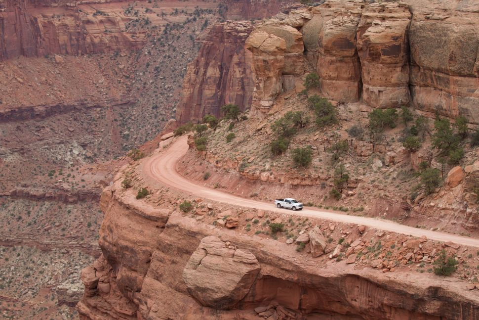 A truck makes its way along a dirt road on the edge of cliff in Canyonlands National Park, Utah.
