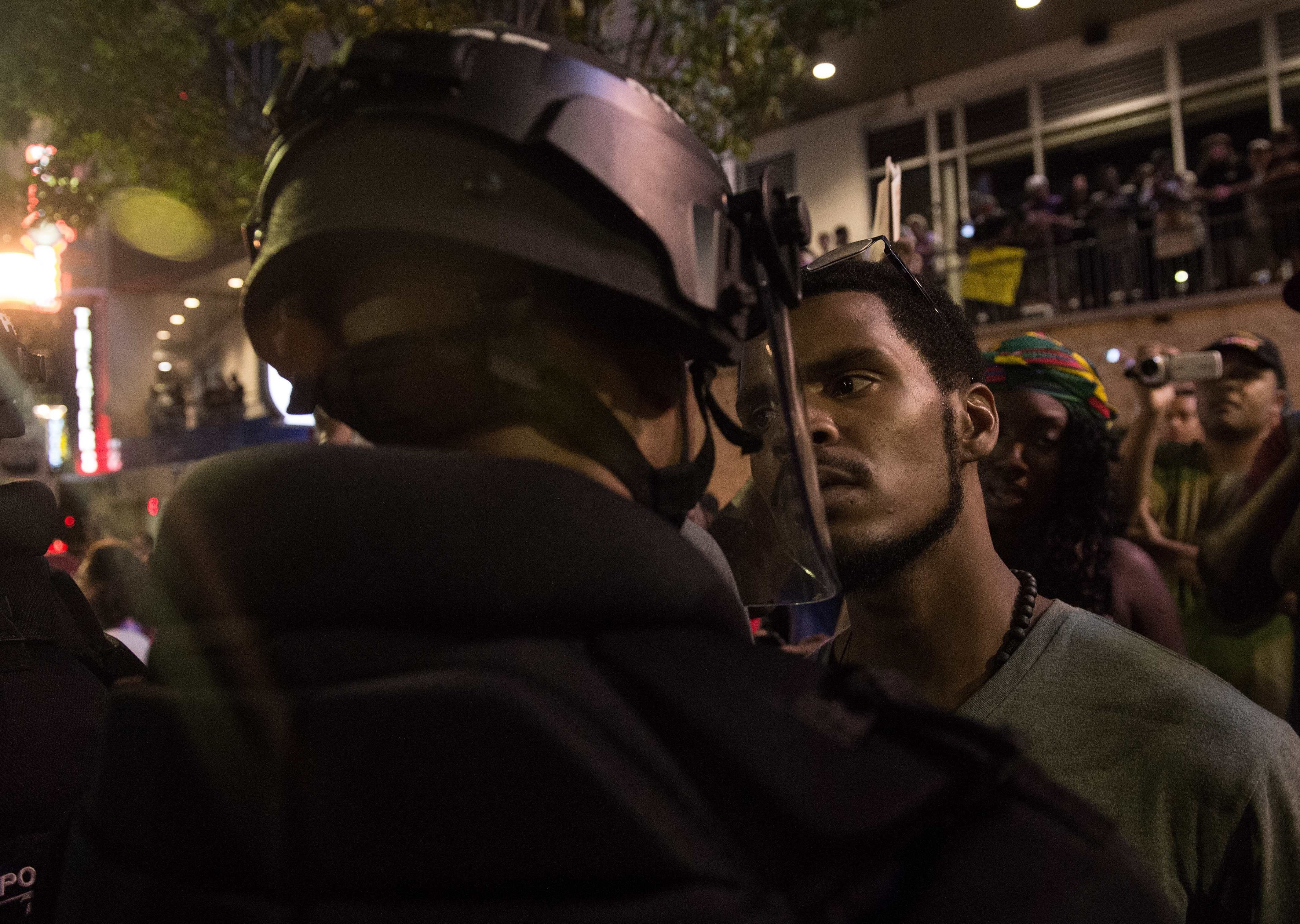 A protester stares at riot police during a demonstration against police brutality in Charlotte, North Carolina, on September 21, 2016, following the shooting of Keith Lamont Scott the previous day. A protester in Charlotte, North Carolina was fatally shot by a civilian during a second night of unrest after the police killed a black man, officials said. / AFP / NICHOLAS KAMM        (Photo credit should read NICHOLAS KAMM/AFP/Getty Images)