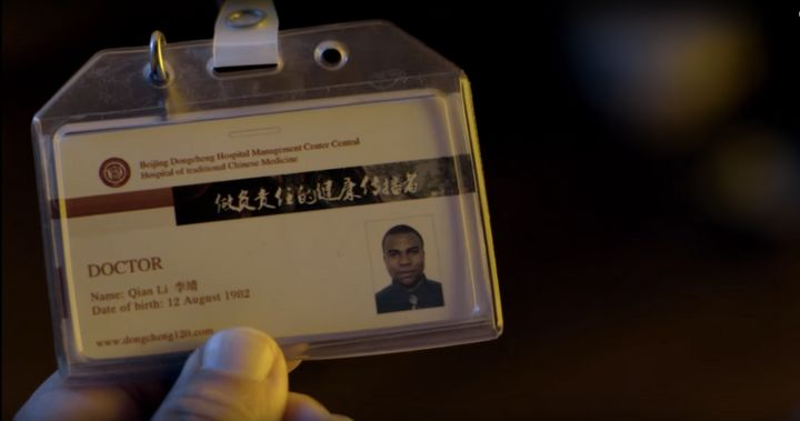 A Chinese man holds up the identification card of an African doctor working and living in China. The image is from Carl Houst